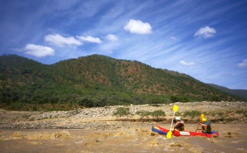 "Two paddlers in a small inflatable canoe known locally as a ""croc"" navigate one of the calmer sections of the Tugela River."